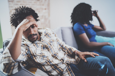 Young sad black couple.Upset man being ignored by partner at home in the living room.American african men arguing with his stylish girlfriend,who is sitting on sofa couch next to him.Blurred Stock Photo - 79489292