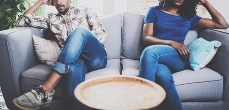 Young displeased black couple.American african men arguing with his stylish girlfriend,who is sitting on sofa on couch next to him with legs crossed.Man looking away offended.Horizontal,cropped.