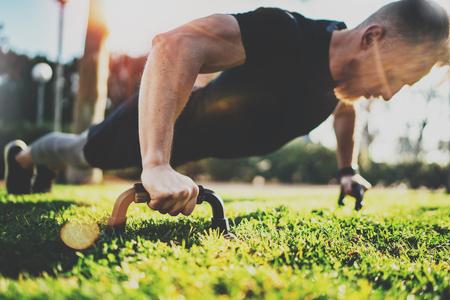Estilo de vida saludable concept.Training outdoors.Handsome deporte atleta hombre haciendo flexiones en el parque en la mañana soleada. Fondo borroso.