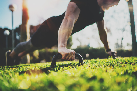 Healthy lifestyle concept.Functional training outdoors.Handsome sport athlete man doing pushups in the park on the sunny morning. Blurred background.Horizontal.Flares,sunlight effect.