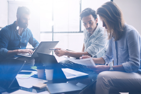 Group of three young coworkers working together in modern coworking studio.Woman pointing on paper document and talking with partners about new startup project.Horizontal,blurred background.