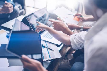 Compañeros de trabajo jovenes que trabajan en el ordenador portátil en la oficina Mujer que lleva a cabo la mano de la tableta y que señala en la pantalla táctil. Horizontal, fondo borroso. Foto de archivo - 79996498