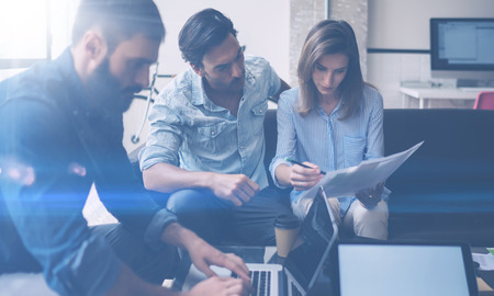 to contemplate: Teamwork process concept.Young coworkers work with new startup project in office.Analyze document, plans.Modern laptop on wood table, papers, documents.Horizontal, blurred, flare Stock Photo