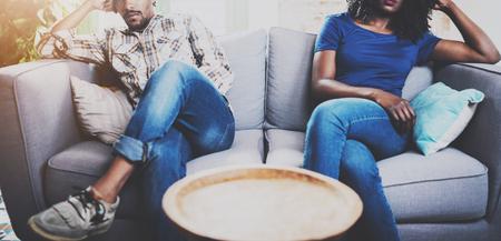 젊은 흑인 커플 불쾌 하 게. 그의 여자 친구와 말다툼을하는 미국 흑인 남자 다리 건너 소파 옆에 소파에 앉아있다. 멀리 그녀의 얼굴에 기분이 식을 찾