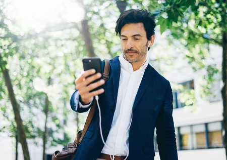 earbud: Attractive smiling businessman using smartphone for listining music while walking in city park.Horizontal,blurred background.