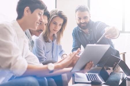 Concept presentatie nieuwe business project.Group van jonge collega's bespreken ideeën met elkaar in modern office.Business mensen met behulp van elektronische apparaten. Horizontale, wazige achtergrond. Stockfoto
