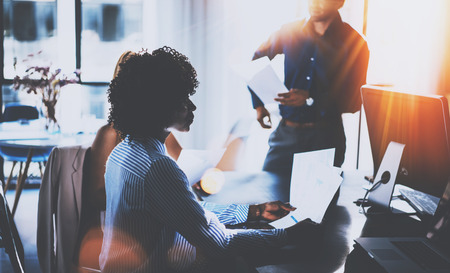 American African woman holding papers hands and talking with partners.Young team of coworkers making great business discussion in modern coworking office.Horizontal, blurred background,flares.