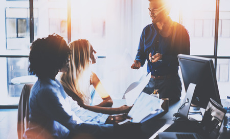Young team of coworkers making great meeting discussion in modern coworking office.Hispanic businessman talking with two business womans.Teamwork concept.Horizontal,blurred background,flares effect. Stock Photo