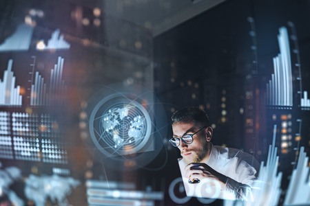 Concept of digital diagram,graph interfaces,virtual screen,connections icon.Young entrepreneur working at modern office.Man using contemporary laptop at night,blurred background.Horizontal. Stockfoto