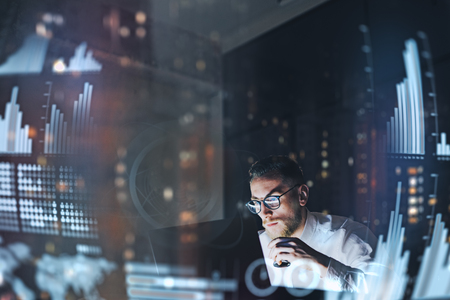Concept of digital diagram,graph interfaces,virtual screen,connections icon.Young finance analist working at modern office.Man using contemporary laptop at night,blurred background.Horizontal.