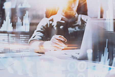 Concept of digital diagram,graph interfaces,virtual screen,connections icon.Young man working at modern office with paper document.Businessman using contemporary laptop.Blurred background.Flares.