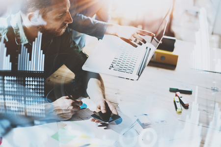 Business people working process concept.Young coworkers working together in modern office.Man using mobile smartphone.Concept of digital diagram,graph interfaces,connections icon.Blurred background.