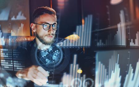 デジタル ダイアグラム、グラフのインターフェイス、仮想画面、接続アイコンの概念。モダンなオフィスで働いている青年実業家。夜にぼかした背 写真素材