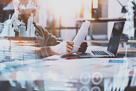 Concept of digital diagram,graph interfaces,virtual screen,connections icon.Young entrepreneur working at modern office with paper document.Man using contemporary laptop,blurred background.Horizontal.