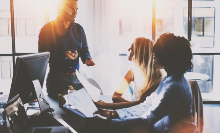 Young team of coworkers making great meeting discussion in modern sunny office.Teamwork concept.Hispanic businessman talking with two colleague woman.Horizontal,blurred background,flare effect.