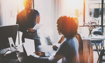 Teamwork concept.Hispanic businessman talking with two colleague woman.Young team of coworkers making great meeting discussion in modern sunny office.Horizontal,blurred background,sun flare effect.