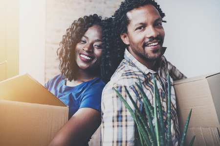 Closeup view of Young black african man and his girlfriend moving boxes into new house together and making a beautiful life.Cheerful family standing in empty new apartment.Blurred background.Flares. Stock Photo