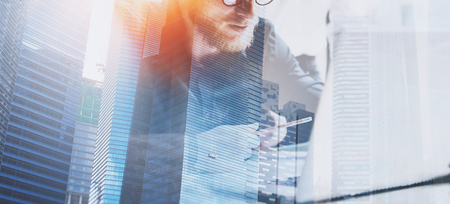 Businessman working process at modern office.Young coworker working at the wooden table with laptop computer.Double exposure,skyscraper building blurred background.Horizontal wide.Flares effect Stock Photo
