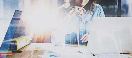 Processus de travail d'une jeune femme d'affaires au poste de bureau moderne. Responsable du travail à la table en bois avec des documents papier. Exposition double, gratte-ciel de fond flou évanoui. Effet flambant profond. Banque d'images - 80529951