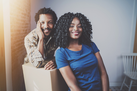 Happy young black african couple moving boxes into new apartment together and making a beautiful life.Cheerful family sitting in empty new home.Horizontal.Blurred background.Flares.