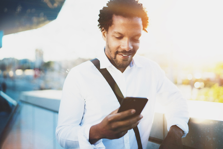Smiling American African man using smartphone to call his friends at sunny city while his brake.Concept of happy young handsome people enjoying gadgets outdoor.Blurred background.Flares