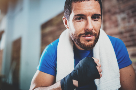 Portrait of Young attractive athlete tying black boxing bandages.Boxer man prepairing before kickboxing training. Blurred background. Horizontal.