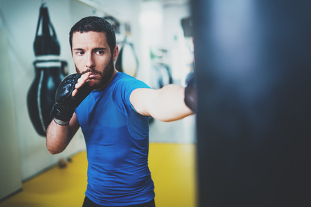 Young muscular kickboxing fighter practicing kicks with punching bag.Boxing on blurred background.Concept of a healthy lifestyle.Horizontal.