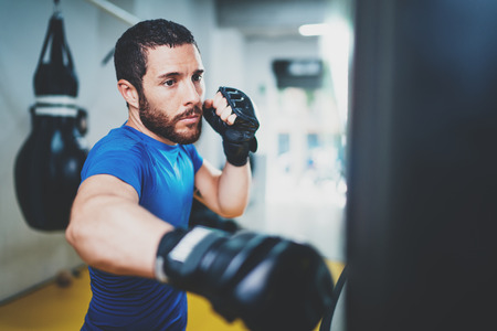 Young muscular kickboxing fighter practicing kicks with punching bag.Kick boxer boxing as exercise for the fight.Boxer hits punching bag.Concept of a healthy lifestyle.Horizontal.