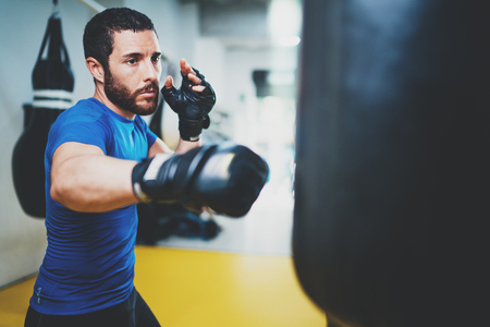 Concept of a healthy lifestyle.Young muscular man fighter practicing kicks with punching bag.Kick boxer boxing as exercise for the fight.Boxer hits punching bag.Horizontal. Stock fotó