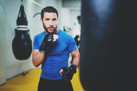 Concept of a healthy lifestyle.Young athlete fighter practicing kicks with punching bag.Kick boxer boxing as exercise for the fight.Boxer man hits punching bag.Horizontal. Stock fotó
