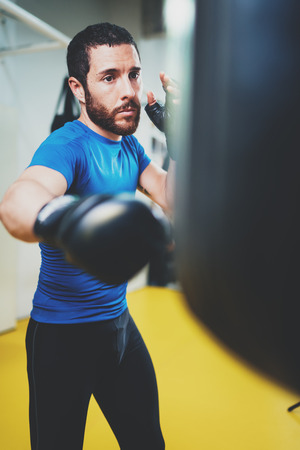 Concept of a healthy lifestyle.Young athlete fighter practicing kicks with punching bag.Kick boxer boxing as exercise for the fight.Boxer man hits punching bag.Vertical. Stock fotó
