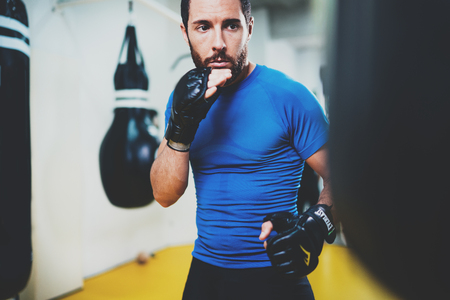 Concept of a healthy lifestyle.Young muscular man fighter practicing kicks with punching black bag.Kick boxer boxing as exercise for the fight.Boxer hits punching bag in gym.Horizontal.