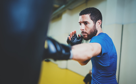 Concept of a healthy lifestyle.Bearded muscular man fighter practicing kicks with punching black bag.Kick boxer boxing as exercise for the fight.Boxer hits punching bag in gym.Horizontal.