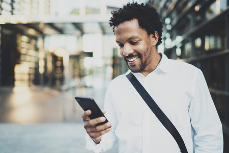 holding hands while walking: Smiling African American while walking at the city holding mobile phone in hands and checking email.Blurred background.