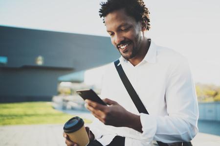 Het portret van de Glimlachende Amerikaanse Afrikaanse mens in hoofdtelefoon bij zonnige stad met koffie haalt binnen kop weg en geniet van aan muziek op zijn smartphone te luisteren Vage achtergrond. Stockfoto