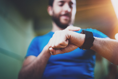 Giovane atleta sorridente che controlla le calorie bruciate sull'applicazione astuta elettronica dell'orologio dopo la buona sessione di allenamento dell'interno nella palestra di forma fisica Fondo vago Effetto delle piume. Archivio Fotografico - 81768509