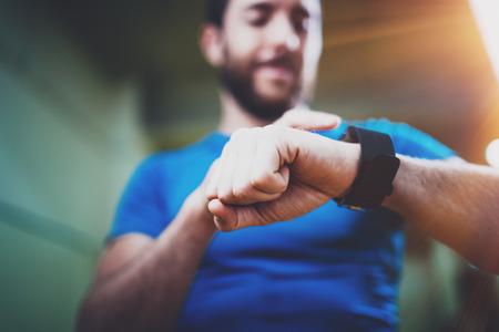 Jeune athlète souriant vérifiant les calories brûlées sur l'application de la montre intelligente électronique après une bonne séance d'entraînement en salle de fitness. Arrière-plan flou. Banque d'images - 81768509
