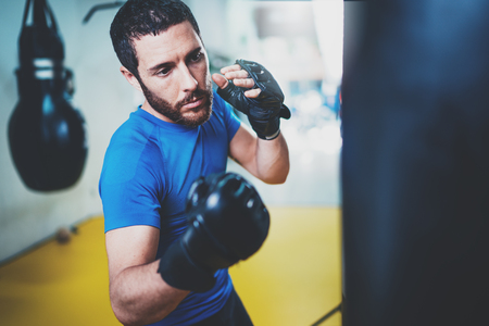 Young boxer doing some training on punching bag at gym. Bearded caucasian boxer training with punching bag in gym.Concept of a healthy lifestyle.Horizontal. 版權商用圖片 - 81768464
