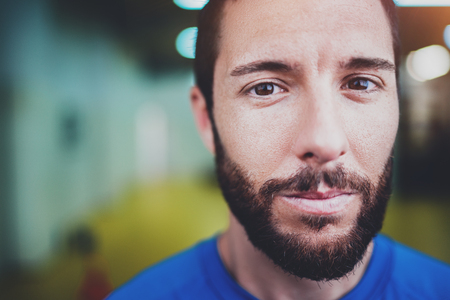 Workout indoor lifestyle concept.Portrait of young bearded man athlete standing in fitness gym on blurred background.Horizontal.