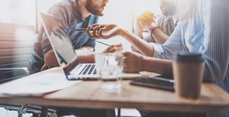 Brainstormproces op kantoor. Jonge collega's werken samen moderne kantoorstudio. Jonge mensen maken gesprek aan houten tafel. Horizontale breed. Vage achtergrond.