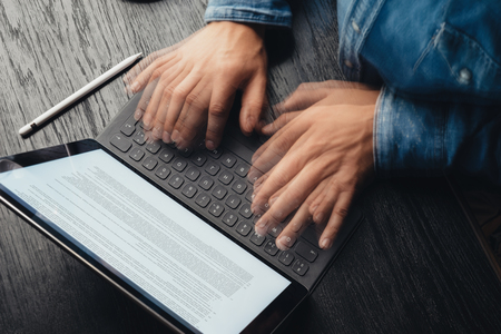 Closeup view of male hands fast typing on electronic tablet keyboard-dock station. Business information on device screen. Man working at office.Horizontal,top view.