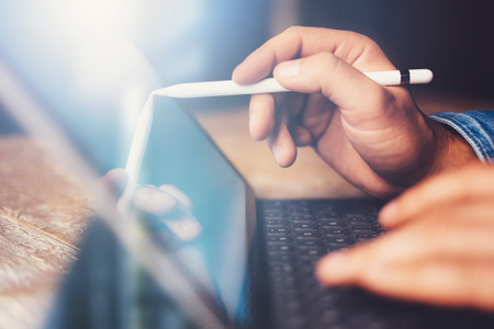 Man using contemporary electronic tablet keyboard-dock station while sitting at the wooden table at office.Men using digital stylus pointing to device screen.Blurred background. Horizontal closeup. Foto de archivo