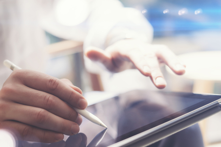 Closeup view of man holding digital tablet on hand and using electronic pen while working at sunny office.Pointing tablet screen.Blurred background.Horizontal.