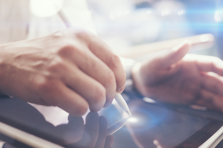Closeup view of man holding digital tablet on hand and using electronic pen while working at sunny office.Pointing tablet screen.Blurred background.Horizontal.Visual effects. Stock Photo