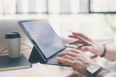 Businessman working at office.Closeup view of male hands typing on electronic tablet keyboard-dock station. Business text information on device screen.Horizontal.Blurred background. Stock Photo