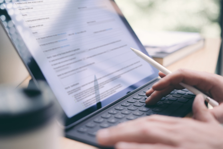 Blogger using mobile touchpad for work.Closeup view of male hands typing electronic tablet keyboard-dock station.Horizontal, blurred background.