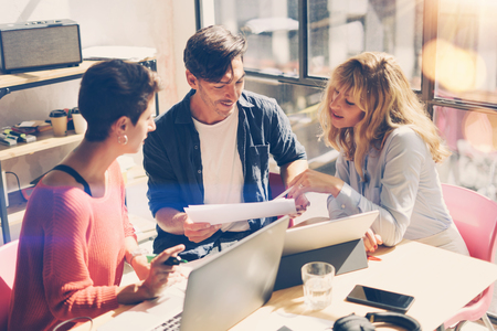 Young entrepreneurs making great conversation during work process in modern office.Business people meeting concept.Blurred background.Horizontal.
