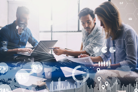 Concept of digital diagram,graph interfaces,virtual screen,connections icon on blurred background.Group of three young coworkers working together at modern coworking studio.Horizontal.
