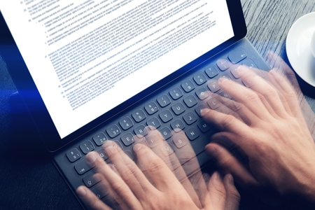 Closeup view of male hands quickly typing on electronic tablet keyboard-dock station. text information on device screen. Man working at office.Horizontal,cropp. Stock Photo