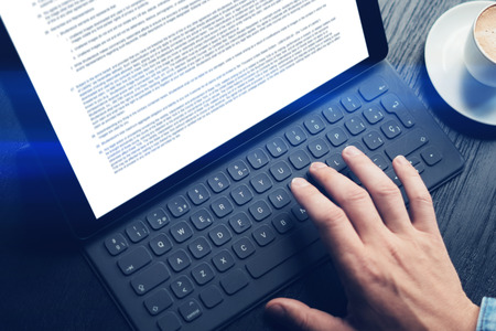 Closeup view of male hands typing on electronic tablet keyboard-dock station. Text information on device screen. Man working at office.Horizontal. 版權商用圖片